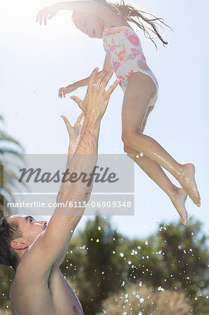 Father and daughter playing in swimming pool Stock Photo - Premium Royalty-Free, Image code: 6113-06909348