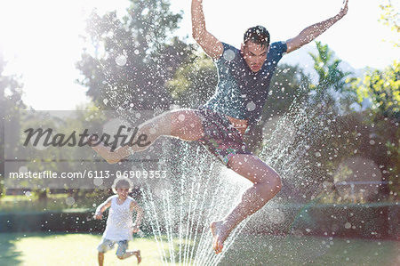 Father and son playing in sprinkler in backyard Stock Photo - Premium Royalty-Free, Image code: 6113-06909353
