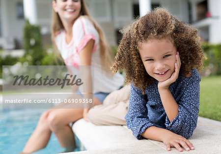 Mother and daughter relaxing by swimming pool Stock Photo - Premium Royalty-Free, Image code: 6113-06909358