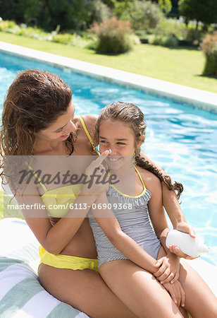 Mother applying sunscreen to daughter's nose Stock Photo - Premium Royalty-Free, Image code: 6113-06909368
