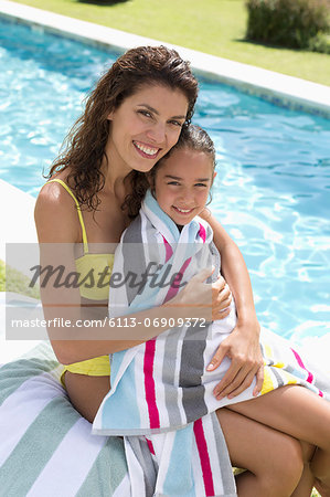 Mother and daughter relaxing by swimming pool Stock Photo - Premium Royalty-Free, Image code: 6113-06909372
