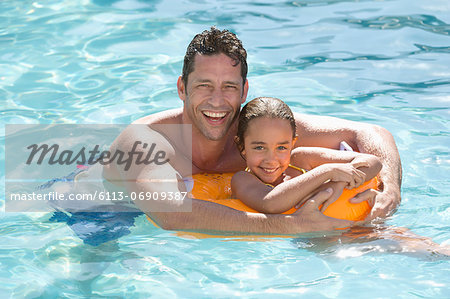 Father and daughter relaxing in swimming pool Stock Photo - Premium Royalty-Free, Image code: 6113-06909387