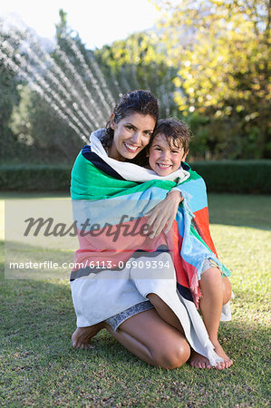 Mother and son wrapped in towel in backyard Stock Photo - Premium Royalty-Free, Image code: 6113-06909394