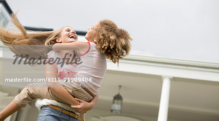 Mother and daughter playing outdoors Stock Photo - Premium Royalty-Free, Image code: 6113-06909408