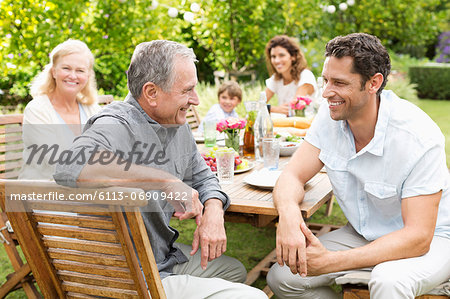 Family sitting at table outdoors Stock Photo - Premium Royalty-Free, Image code: 6113-06909422