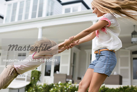 Mother and daughter playing outside house Stock Photo - Premium Royalty-Free, Image code: 6113-06909439