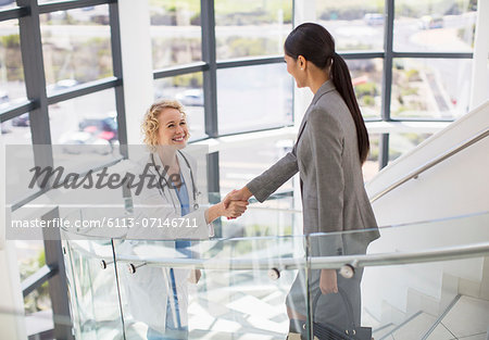 Doctor and businesswoman handshaking on stairs in hospital Stock Photo - Premium Royalty-Free, Image code: 6113-07146711