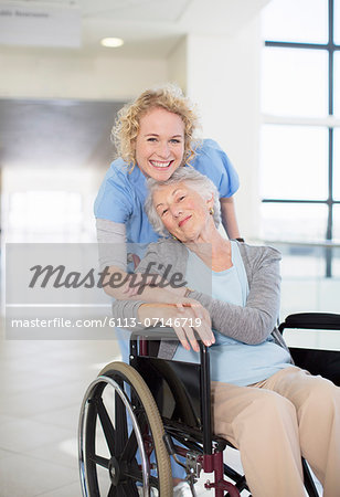 Portrait of smiling nurse and elderly patient in wheelchair