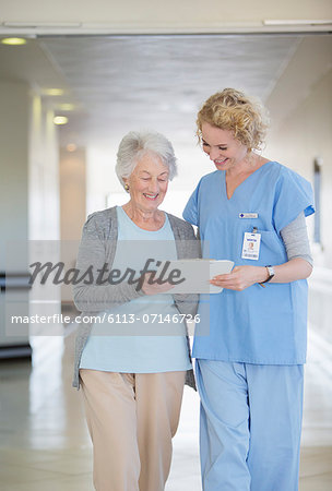 Nurse and aging patient reading chart in hospital corridor