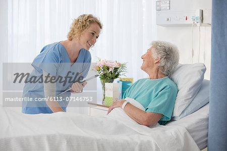 Nurse and aging patient talking in hospital room