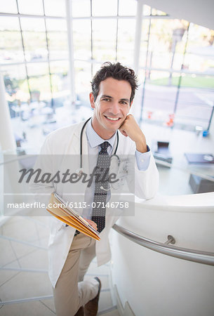 Portrait of smiling doctor on stairs in hospital Stock Photo - Premium Royalty-Free, Image code: 6113-07146758