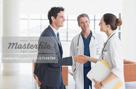 Doctor and businessman handshaking in hospital lobby Stock Photo - Premium Royalty-Free, Image code: 6113-07146784