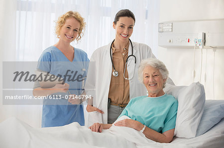 Doctor, nurse and senior patient smiling in hospital room