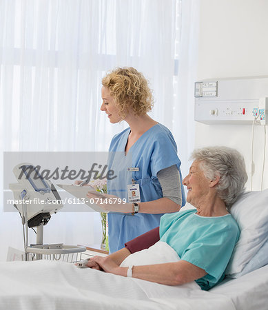 Nurse checking equipment in aging patient's hospital room