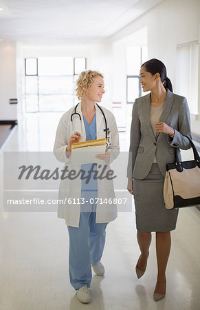 Doctor and businesswoman walking in hospital corridor Stock Photo - Premium Royalty-Free, Image code: 6113-07146807