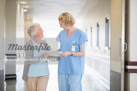 Nurse and senior patient talking in hospital corridor