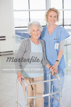 Portrait of smiling nurse and senior patient with walker