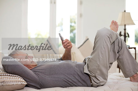 Senior man using cell phone on bed Stock Photo - Premium Royalty-Free, Image code: 6113-07146874