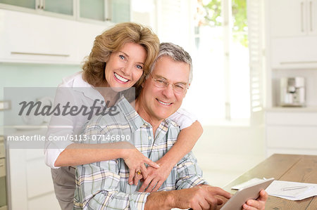 Portrait of smiling senior couple with digital tablet in kitchen Stock Photo - Premium Royalty-Free, Image code: 6113-07146890