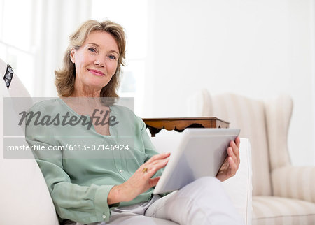 Portrait of senior woman using digital tablet on sofa Stock Photo - Premium Royalty-Free, Image code: 6113-07146924