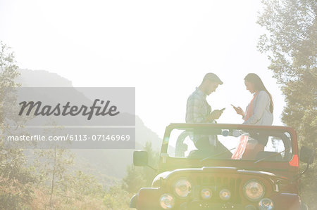 Couple using cell phones in sport utility vehicle Stock Photo - Premium Royalty-Free, Image code: 6113-07146969