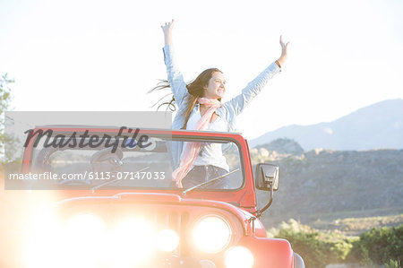 Woman cheering in sport utility vehicle Stock Photo - Premium Royalty-Free, Image code: 6113-07147033