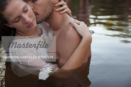 Sensual couple kissing in lake Stock Photo - Premium Royalty-Free, Image code: 6113-07147126