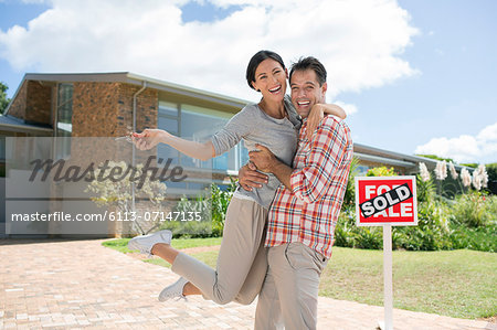 Portrait of enthusiastic couple hugging outside house with For Sale sign Stock Photo - Premium Royalty-Free, Image code: 6113-07147135
