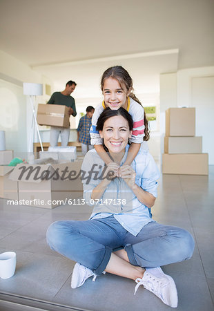 Portrait of smiling mother and daughter among cardboard boxes Stock Photo - Premium Royalty-Free, Image code: 6113-07147138