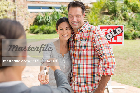Realtor giving couple keys to new house Stock Photo - Premium Royalty-Free, Image code: 6113-07147148