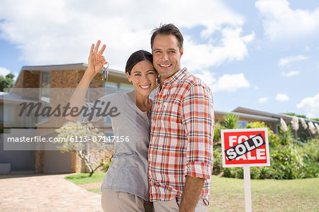 Portrait of smiling couple holding keys in front of new house Stock Photo - Premium Royalty-Free, Image code: 6113-07147156