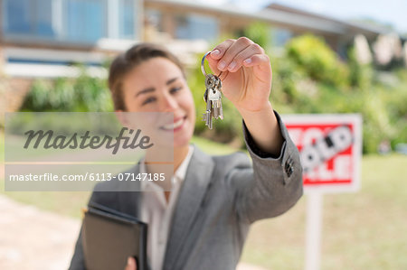 Portrait of realtor holding house keys in front of house Stock Photo - Premium Royalty-Free, Image code: 6113-07147185