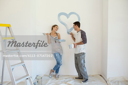 Couple painting blue heart on wall Stock Photo - Premium Royalty-Free, Image code: 6113-07147202