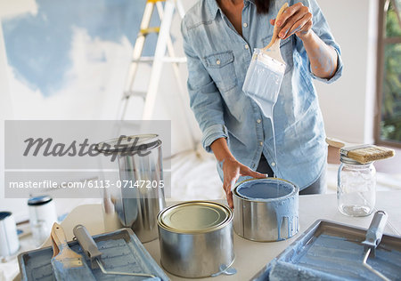 Woman holding paintbrush with blue paint Stock Photo - Premium Royalty-Free, Image code: 6113-07147205