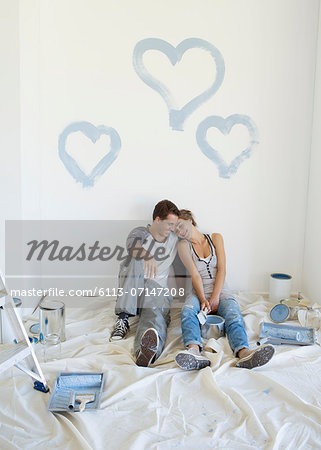 Couple painting blue hearts on wall Stock Photo - Premium Royalty-Free, Image code: 6113-07147208