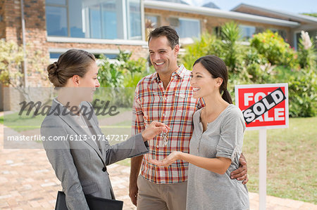 Realtor giving couple keys to new house Stock Photo - Premium Royalty-Free, Image code: 6113-07147217