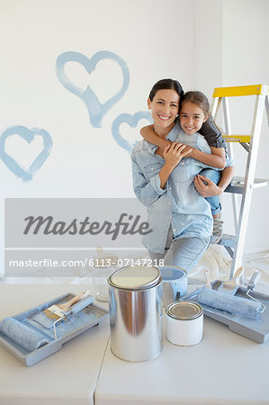 Mother and daughter hugging among paint supplies Stock Photo - Premium Royalty-Free, Image code: 6113-07147218