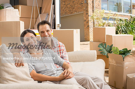 Portrait of smiling couple on sofa near moving van in driveway Stock Photo - Premium Royalty-Free, Image code: 6113-07147224