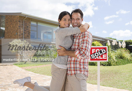Portrait of smiling couple hugging outside new house Stock Photo - Premium Royalty-Free, Image code: 6113-07147233