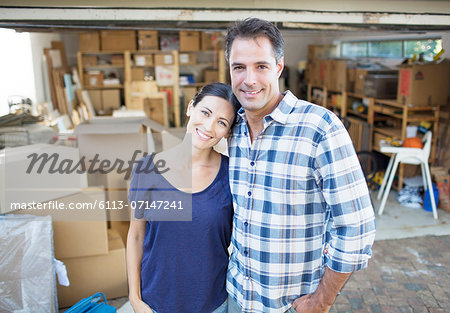 Portrait of smiling couple outside garage among cardboard boxes Stock Photo - Premium Royalty-Free, Image code: 6113-07147241