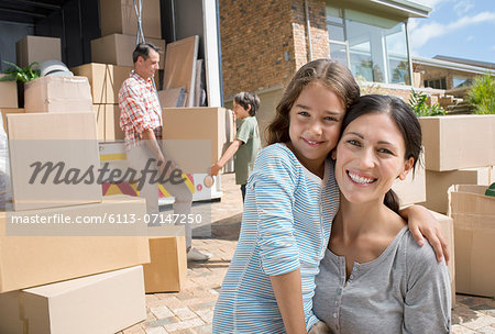 Mother and daughter smiling by moving van in driveway Stock Photo - Premium Royalty-Free, Image code: 6113-07147250