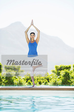 Woman practicing yoga at poolside Stock Photo - Premium Royalty-Free, Image code: 6113-07147363