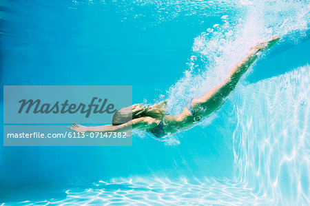 Woman diving into swimming pool Stock Photo - Premium Royalty-Free, Image code: 6113-07147382