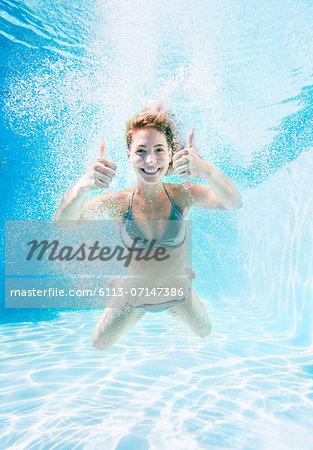 Woman giving thumbs up underwater in swimming pool Stock Photo - Premium Royalty-Free, Image code: 6113-07147386