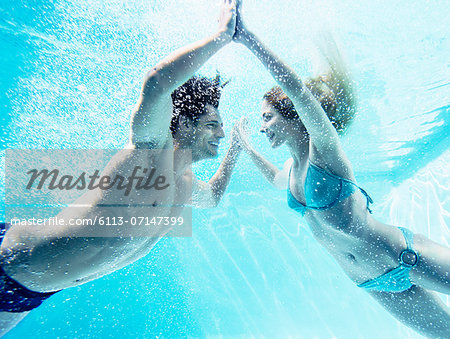 Couple touching hands underwater Stock Photo - Premium Royalty-Free, Image code: 6113-07147399