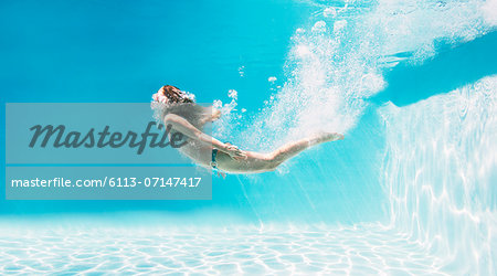 Woman swimming underwater in swimming pool Stock Photo - Premium Royalty-Free, Image code: 6113-07147417