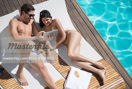 Couple using digital tablet poolside Stock Photo - Premium Royalty-Free, Image code: 6113-07147422