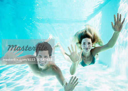 Portrait of smiling couple underwater in pool Stock Photo - Premium Royalty-Free, Image code: 6113-07147423