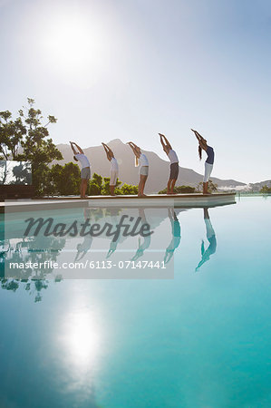 People practicing yoga at poolside Stock Photo - Premium Royalty-Free, Image code: 6113-07147441