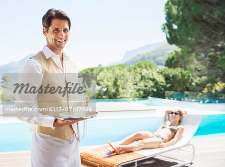 Waiter smiling at poolside Stock Photo - Premium Royalty-Free, Image code: 6113-07147468
